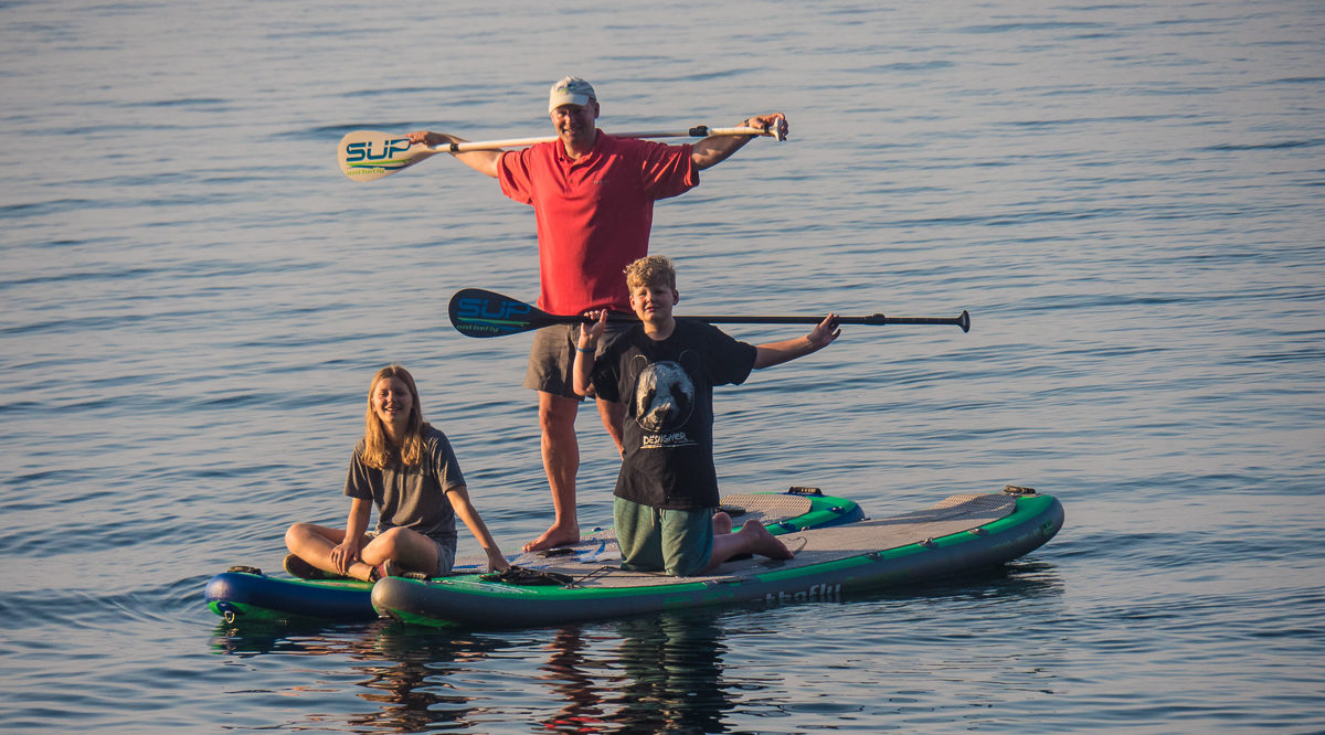 man with grandkids on paddle board